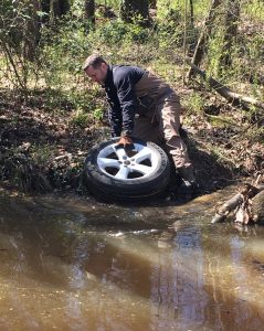 Man pulling a tire out of water