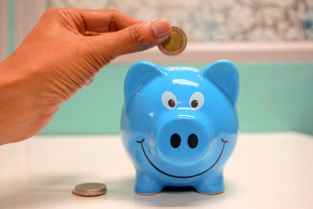blue piggy bank hand coin smiling