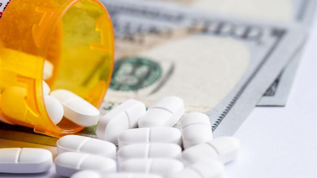 Drug Costs medicine in bottle on money