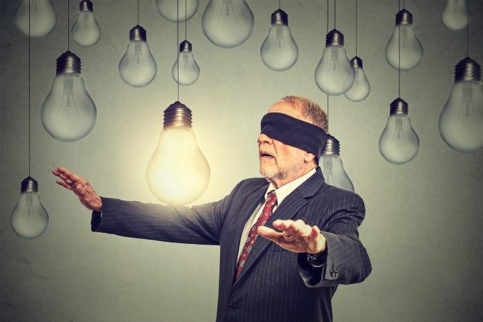 Blind man walking in room of light bulbs