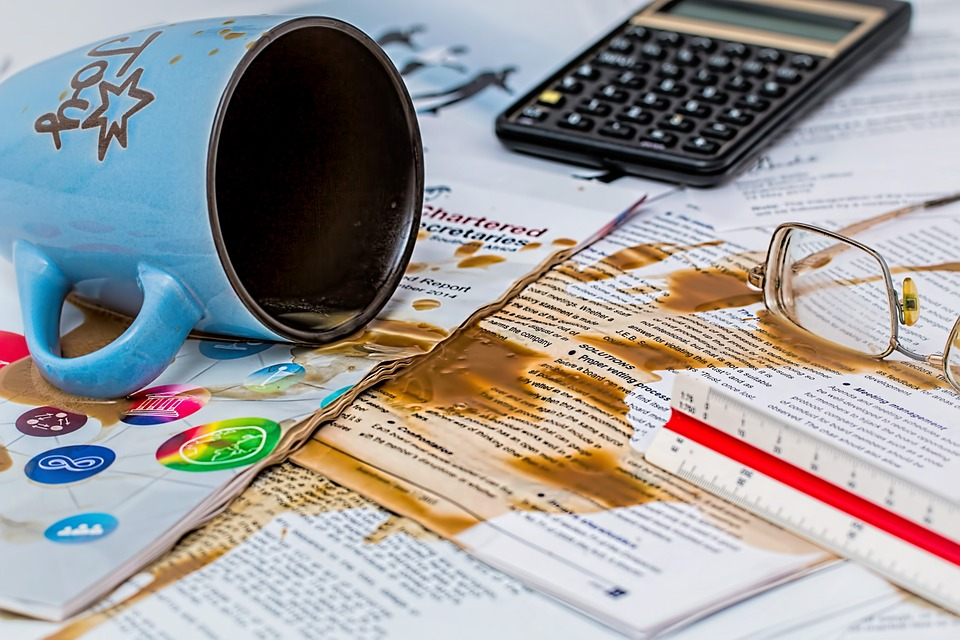 retirement mistakes spilling coffee over desk of papers