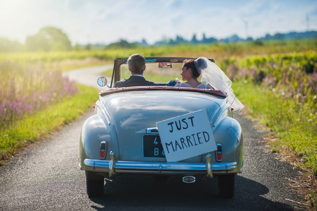 newlyweds driving away in car just married